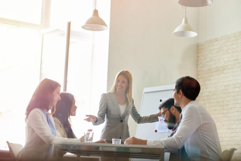 businesswoman shares sales training ideas to group at table