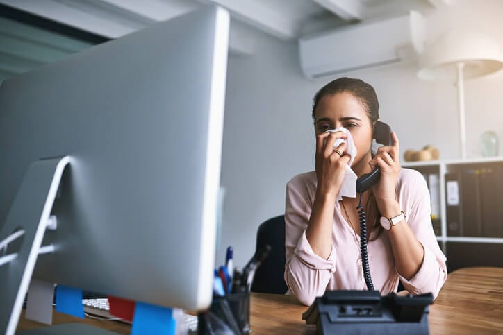 woman blowing her nose over phone needs cold calling tips