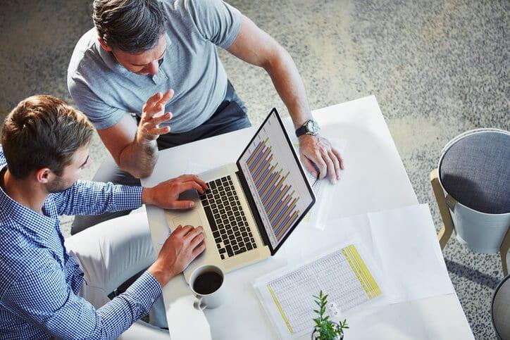 two businessmen looking at intranet metrics on laptop