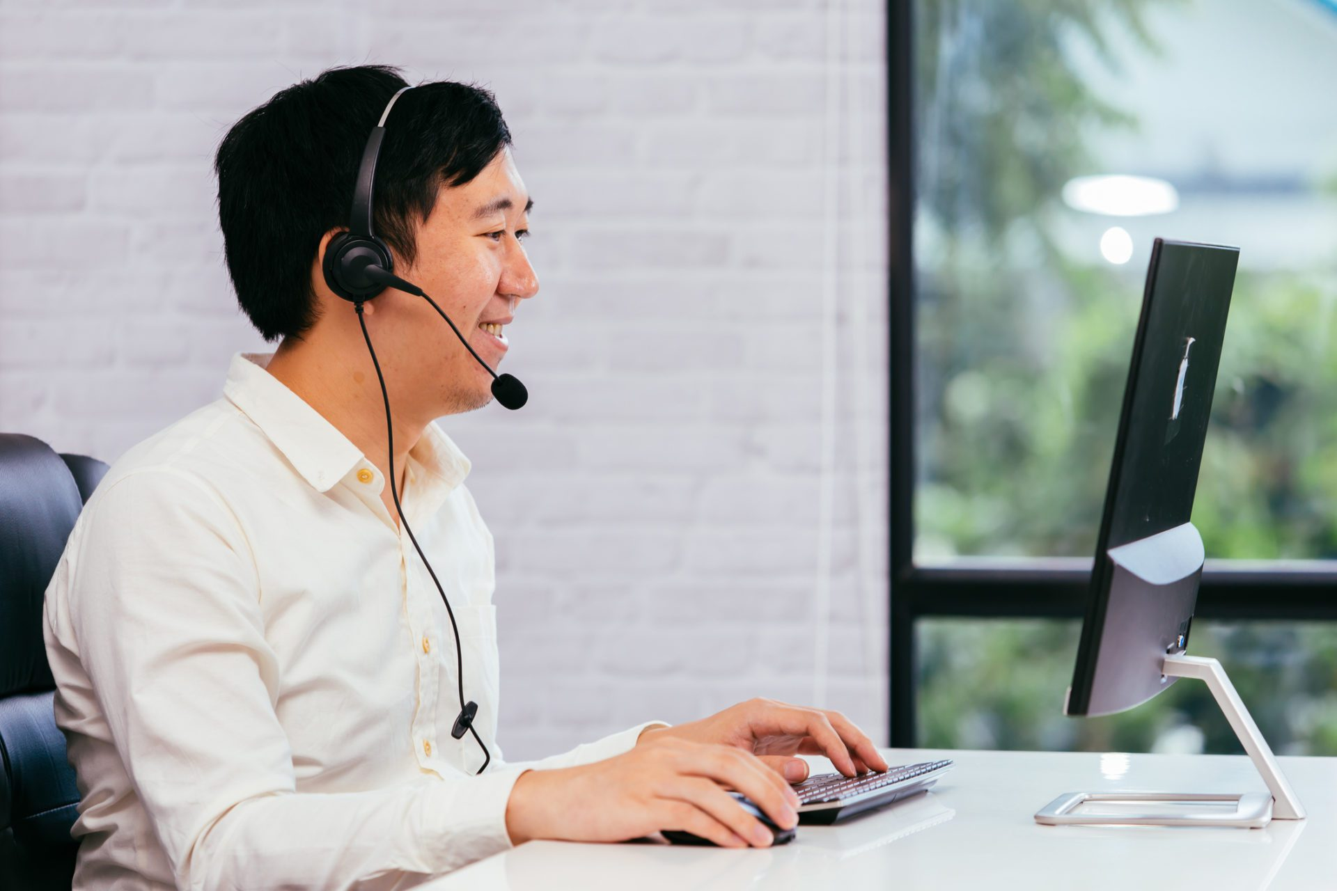 man on headset in office uses new contact center technologies