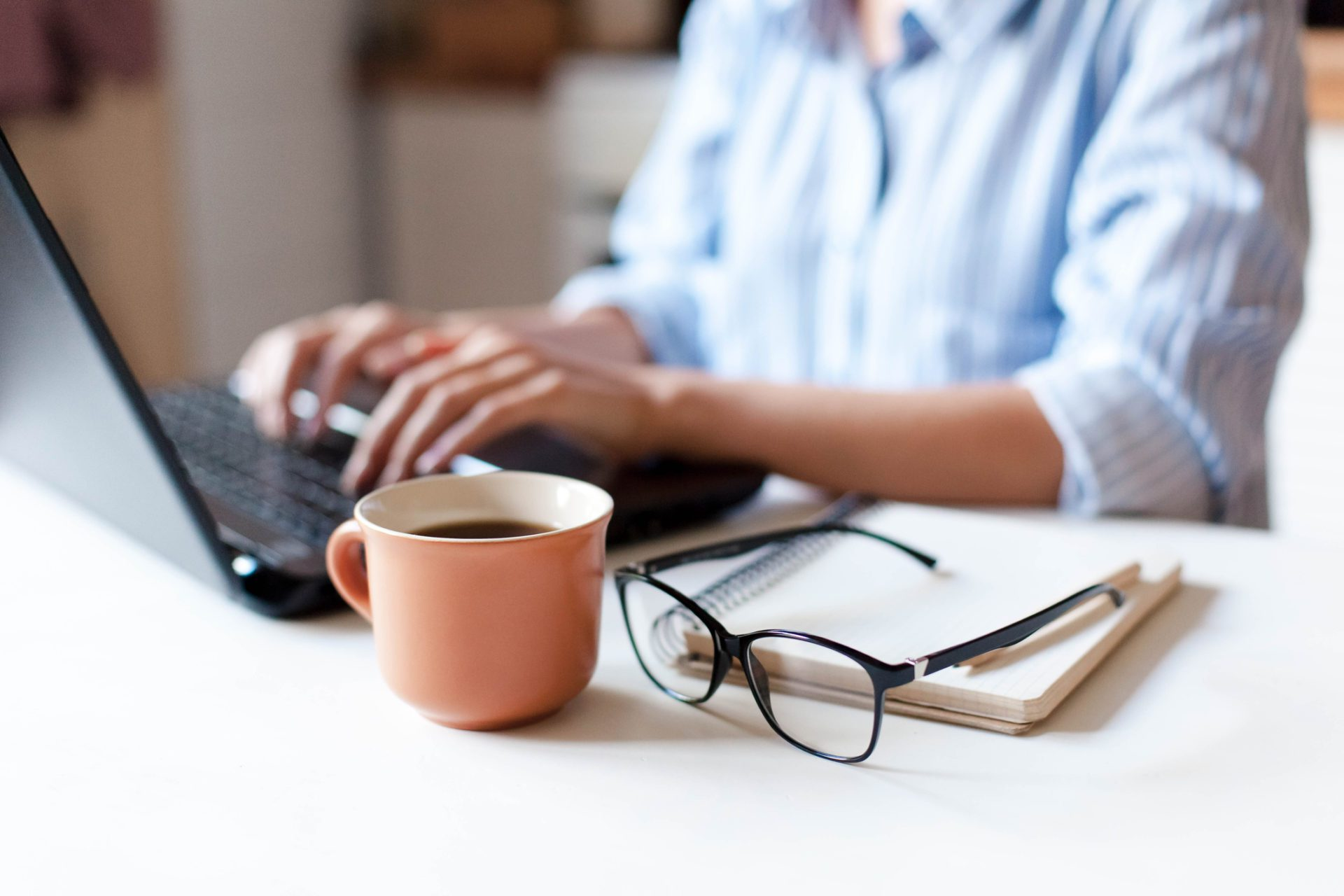 person working on laptop with coffee and glasses in foreground