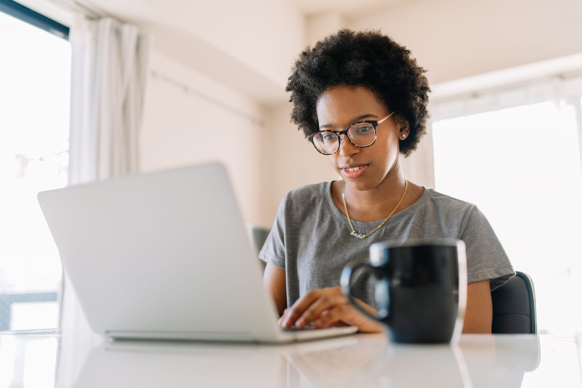 woman browses knowledge management system on laptop at home