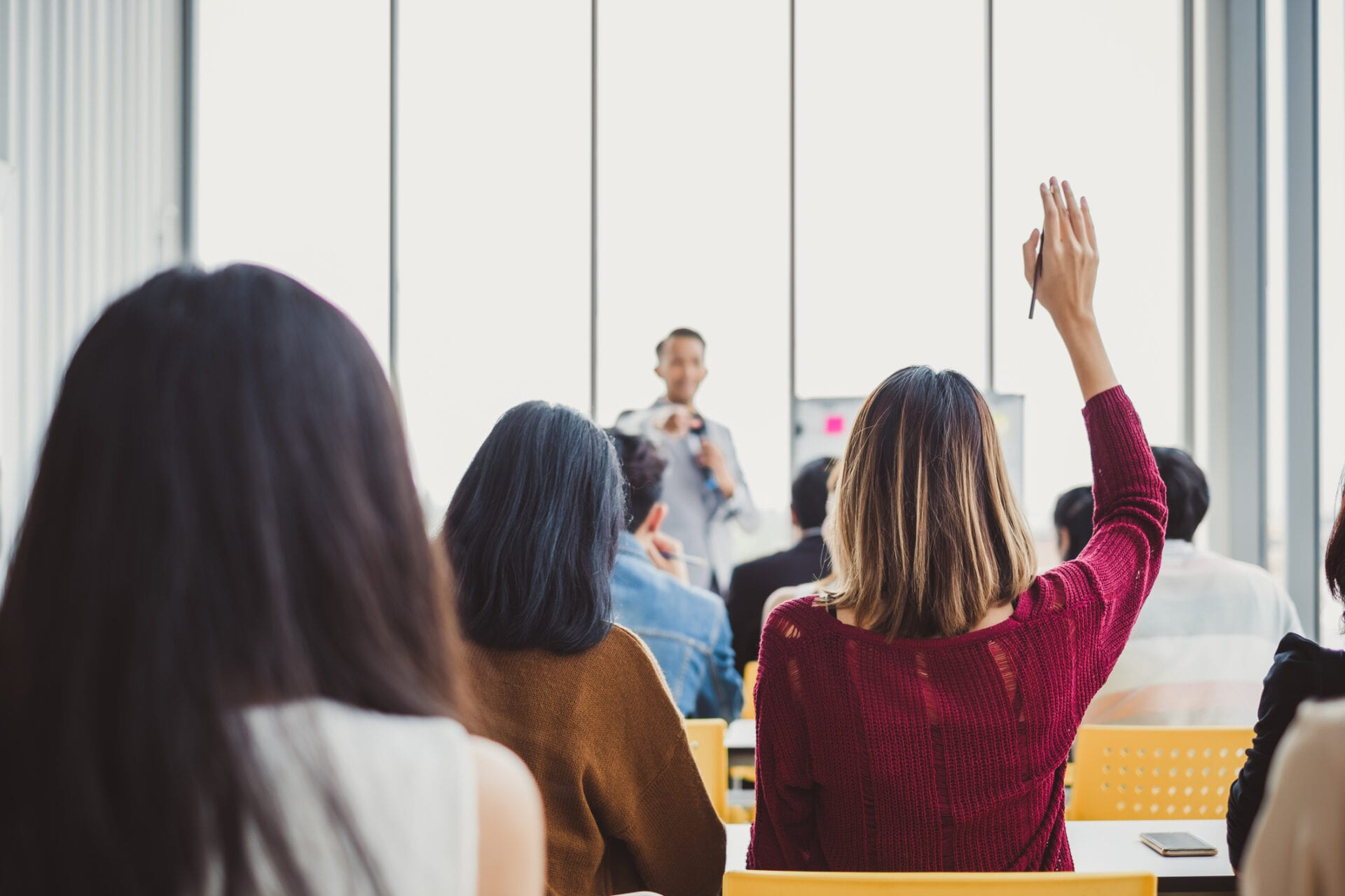 woman raising hand in training session representing concept of cost of training employees