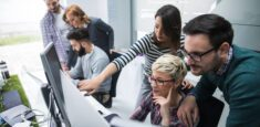 coworkers gathering around desk to share tacit knowledge